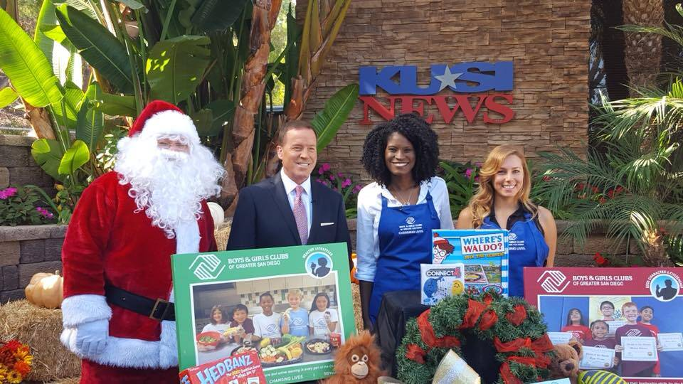 Angel Mason Broadus, President of Puzzle Pieces Marketing stands with Santa and KUSI News for the Boys & Girls Club of San Diego County.