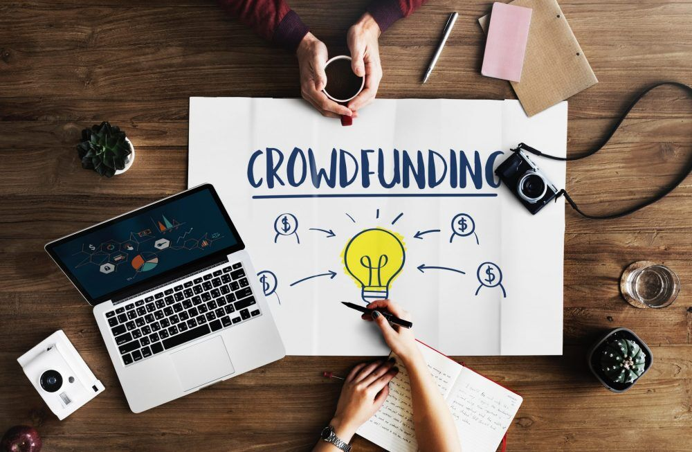 "A white poster titled ""Crowdfunding"", written in marker with $ signs pointing to a yellow light bulb. The poster is on a wooden table that also shows two pairs of hands, one with a coffee cup and another with a pen and journal. On the able are also a laptop, cameras, apple, small cactus plants. The scene look like two co-workers brainstorming of crowdfunding for nonprofits."