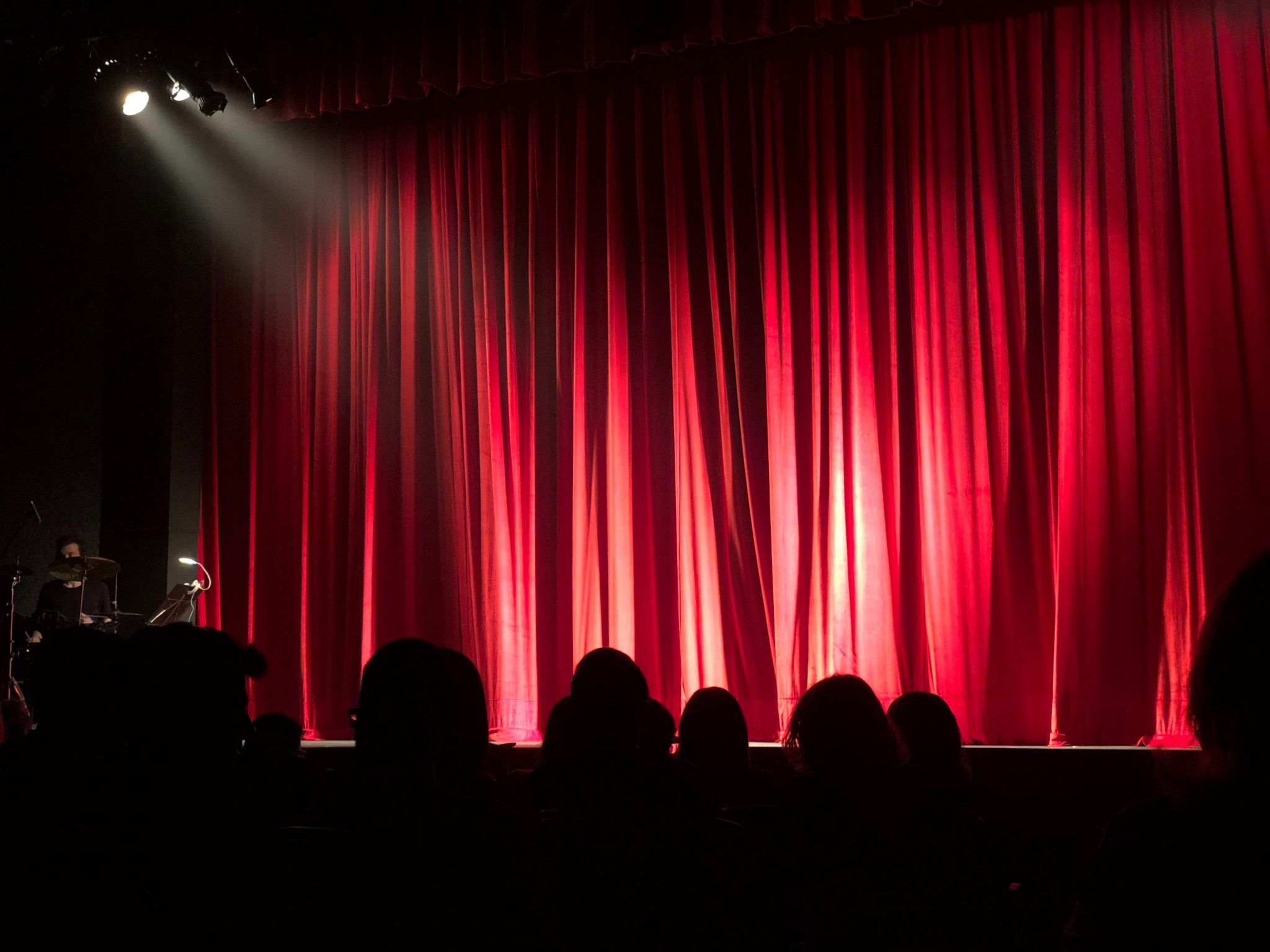 A theatre with an audience in the dark in the foreground and a large red curtain illuminated by stage lights as the focus.