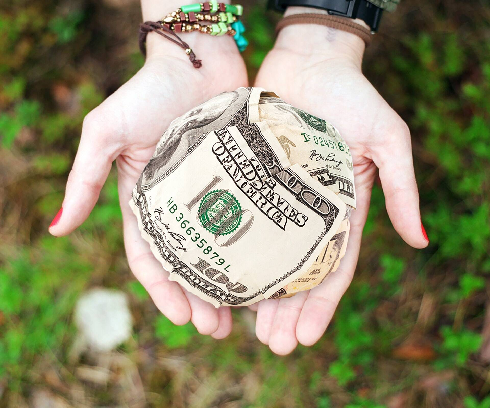 Closeup of a woman's two hands, palms up, holding a giant ball of 100 dollar bills representing nonprofit donor retention.