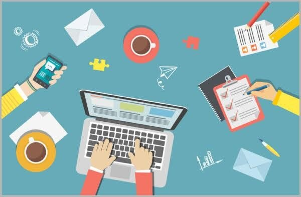 Cartoonish graphic of an aerial shot of a desktop showing a laptop with hands typing, two coffee cups, another hand with a cellphone, another hand creating a checklist, envelopes, pens, puzzle pieces, papers and other items representing digital marketing terms.